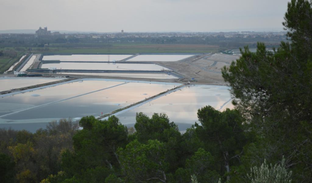 Les bassins de l'usine de traitement de l'uranium de Malvési avec, en arrière-plan, le centre-ville de Narbonne. © François Delotte