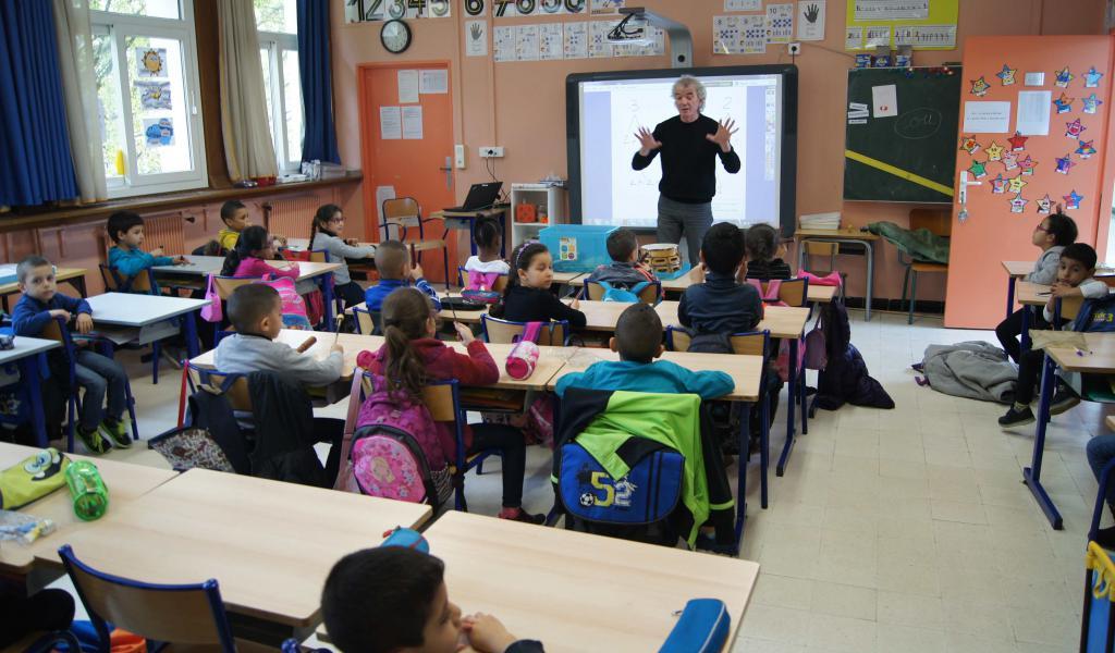 Eveil musical à l'école Jean Moulin de Nîmes. Derrière l'enseignant, un tableau numérique- Crédit : FD / LMDP